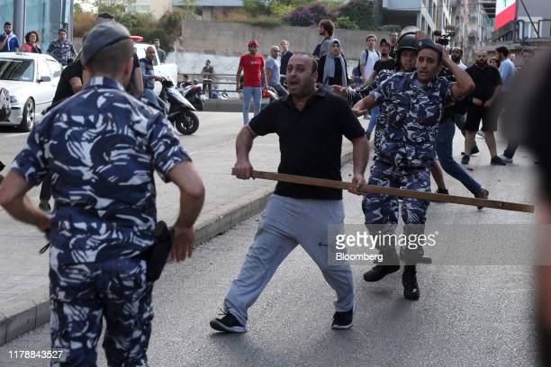 Lebanese riot police tackle an Hezbollah supporter during clashes with antigovernment protesters in Beirut Lebanon on Tuesday Oct 29 2019 I tried...