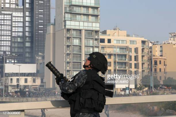 Lebanese riot policeman aims his tear gas gun amid clashes with protesters following a demonstration in central Beirut on June 6, 2020. - Protesters...