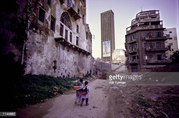 Lebanese schoolchildren walk to school December 15 past buildings partially destroyed during Lebanon's civil war In the background can be seen an...