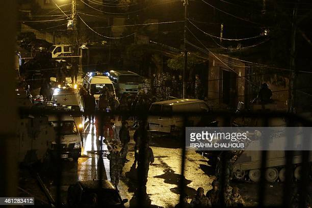 Lebanese security forces and emergency personnel gather outside a cafe targeted by a suicide bombing on January 10 2015 in the Jabal Mohsen Alawite...