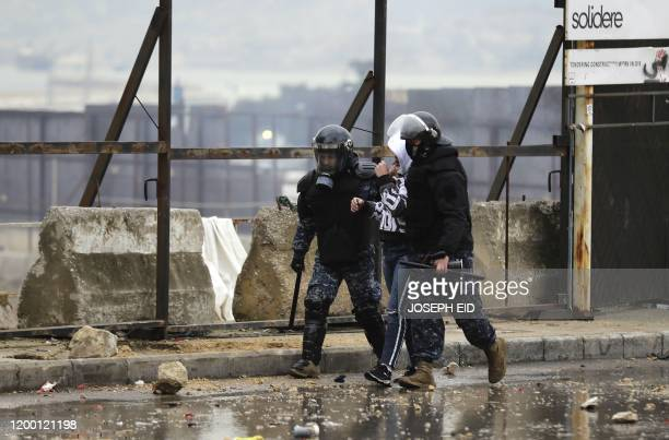 Lebanese security forces arrest a protester during a demonstration in the heart of Beirut to stop a confidence vote for a new government, which they...