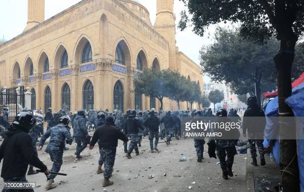 Lebanese security forces run to disperse demonstrators during a protest in the heart of Beirut to stop a confidence vote for a new government, which...