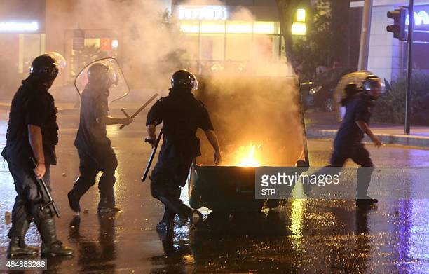 Lebanese security forces run towards a rubbish container set on fire by protesters during clashes following a demonstration organised by the 'You...
