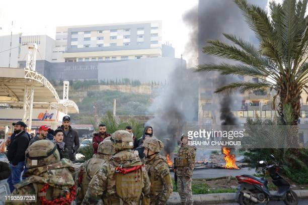Lebanese security forces stand guard as antigovernment protesters set tyres on fire during protests in the northern city of Tripoli on January 14...