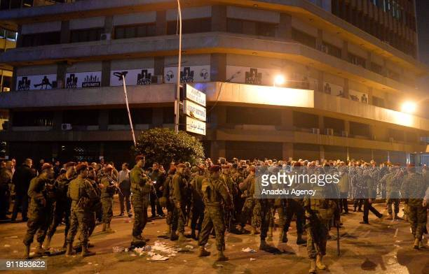 Lebanese security forces take security measures as protesters burn tires used as a road block during a protest to condemn libelous video about...