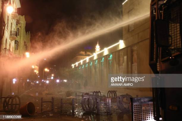 Lebanese security forces use a water cannon to disperse anti-government demonstrators during a protest in the downtown area of the capital Beirut on...