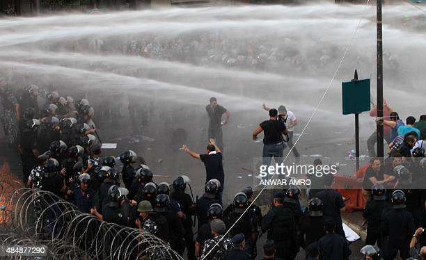 Lebanese security forces use water cannons to disperse protestors demonstrating against the ongoing trash crisis in the capital Beirut on August 22...
