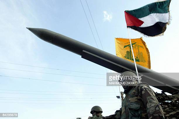 Lebanese Shiite Hezbollah militants parade with a missile as the Palestinian and the movement's flags flutter during an annual parade in the southern...