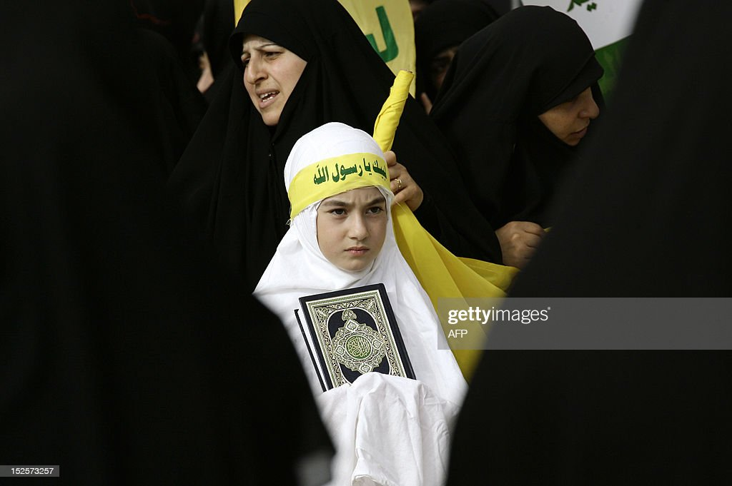 A Lebanese Shiite Muslim girl holds a a copy of the Koran along with supporters of the Hezbollah movement during a demonstration in the southern town of Bint Jbeil on September 22, 2012, to protest...
