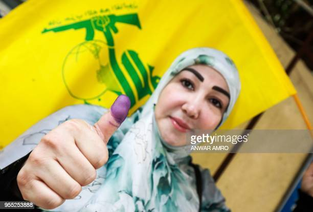 A Lebanese Shiite woman flashes her inkstained thumb and waves a flag of the Shiite Hezbollah movement after voting at a polling station in the...