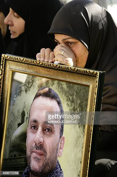 A Lebanese Shiite woman sits with a portrait of her son a member of Lebanon's militant Shiite Muslim movement Hezbollah reportedly killed during...