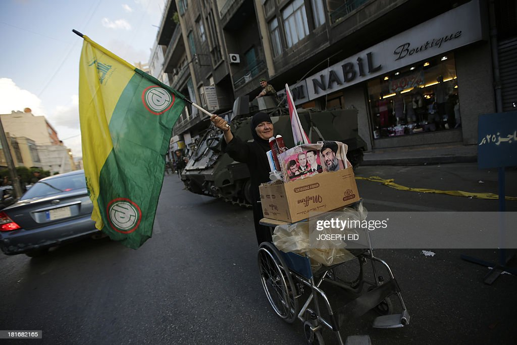 A Lebanese Shiite woman waves a Hezbollah and Amal movements flag as she pushes a cart past a Lebanese army forces checkpoint in the southern suburb of Beirut on September 23, 2013. Lebanese troops are to take over security at checkpoints set up by the Hezbollah movement in their southern Beirut stronghold after two bombings, the interior minister told AFP.