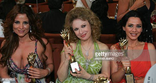 Lebanese singer and actress Carole Samaha Egyptian star Nelly and Syrian actress Sulaf Fawakherji hold their awards during the Murex d'Or award...