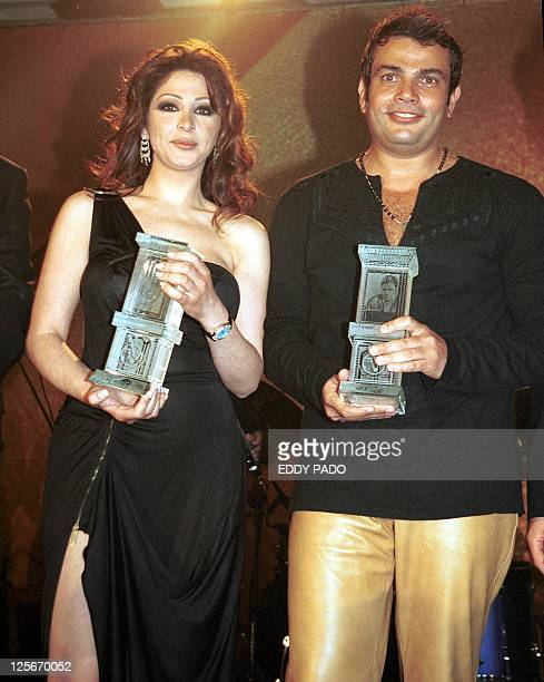 Lebanese singer Elissa and egyptian pop star Amro Diab pose for a picture after receiving honorary awards in Dubai 10 September 2002 AFP PHOTO/Eddy...