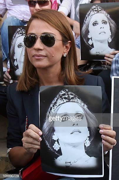 Lebanese singer Julia Boutros holds a portrait of Lebanese diva Fairuz during a sitin in Beirut on July 26 2010 following rumors that the Rahbani...
