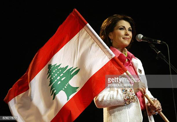 Lebanese singer Magida alRoumi holds a national flag during her performance in downtown Beirut's landmark Martyrs Square late 13 April 2005 as part...