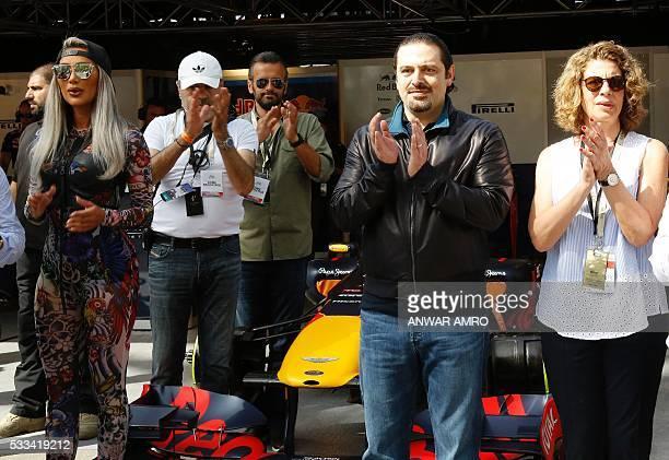 Lebanese singer Maya Diab former Lebanese prime minister Saad Hariri and Lama Salam the wife of the Lebanese prime minister stand next to a Formula...