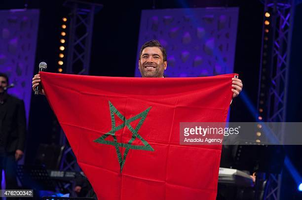 Lebanese singer Wael Kfoury holds a he Moroccan flag as performs on stage at Nahda Concert Hall during the 14th edition of the Mawazine International...