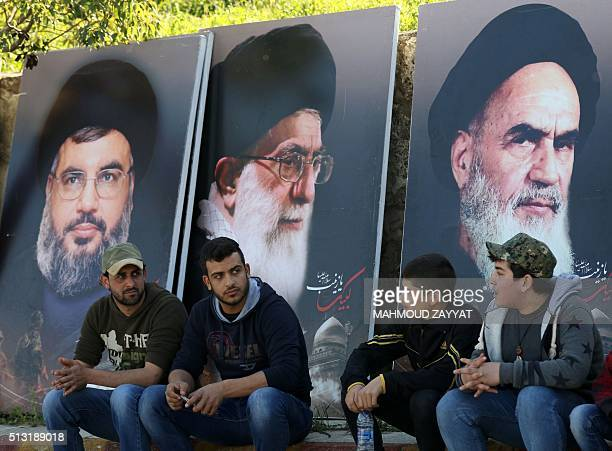 Lebanese sit in front of giant posters bearing portraits of Hassan Nasrallah the head of Lebanon's militant Shiite Muslim movement Hezbollah the...