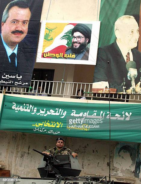 Lebanese soldier guards a polling station under posters of parliamentary candidate Yassin Jaber Hezbollah Secretary General Hassan Nasrallah and...