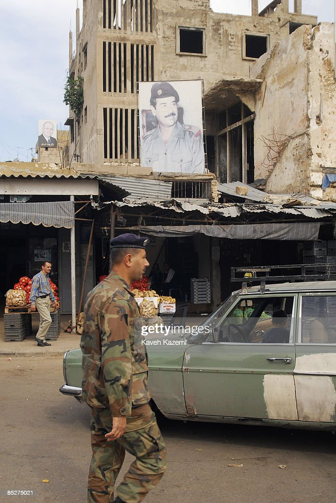 A Lebanese soldier passes by a poster of Saddam Hussein the Iraqi dictator hanging from a wall in a market place in Triploi in northern Lebanon on 9 November 2008. Tripoli has a Suuni majority and is probably the only place on the planet which has a poster of this tyrant displayed in a public place.