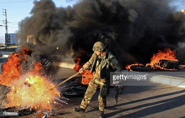 Lebanese soldier removes a buring tire in the town of Marjayoun in south Lebanon 23 January 2007 At least two people were wounded by gunshots at dawn...
