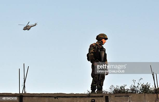 A Lebanese soldier stands guard on a rooftop in the northern Lebanese city of Tripoli on April 2 2014 after Lebanese troops backed by helicopters...