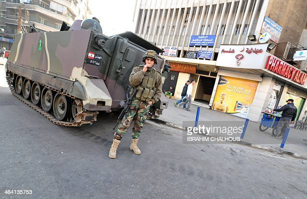 A Lebanese soldier stands next to an armoured personnel carrier in a street of the northern port city of Tripoli on January 21 2014 as part of...
