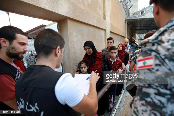 Lebanese soldiers and social workers check Syrian refugees as they prepare to leave the Lebanese capital Beirut to return to their homes in Syria on...