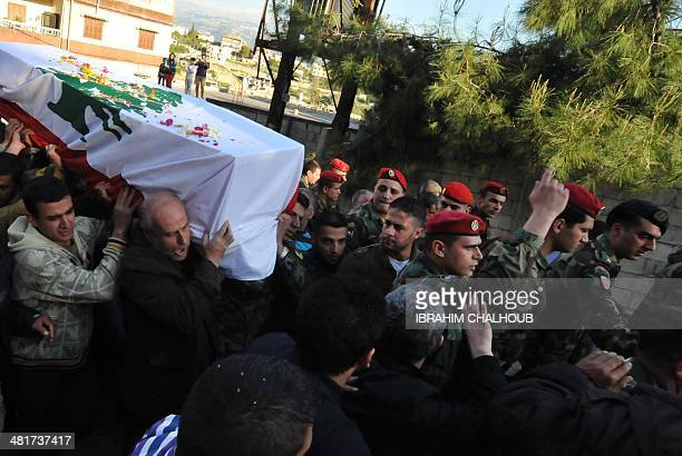 Lebanese soldiers friends and relatives attend the funeral of soldier Abdulqader Awik on March 31 2014 in the northern village of Fawar The soldier...