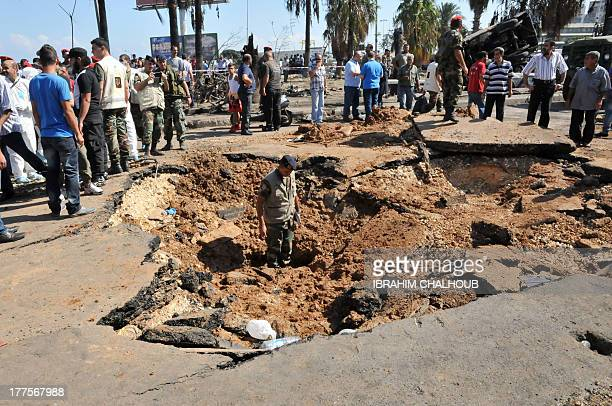 Lebanese soldiers inspect on August 24 2013 the crater left by a bombing outside AlTaqwa mosque in the northern city of Tripoli Lebanon is to observe...