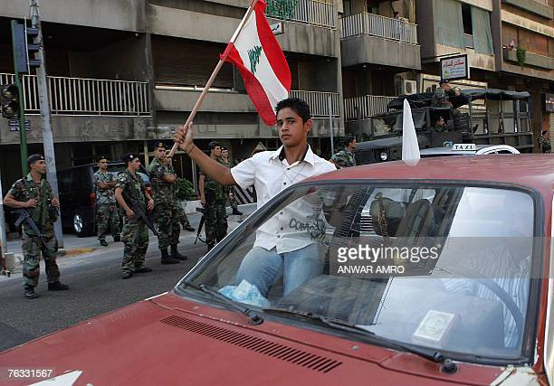 Lebanese Soldiers Stand Guard As A Youth Waves The Flag Out Of Window