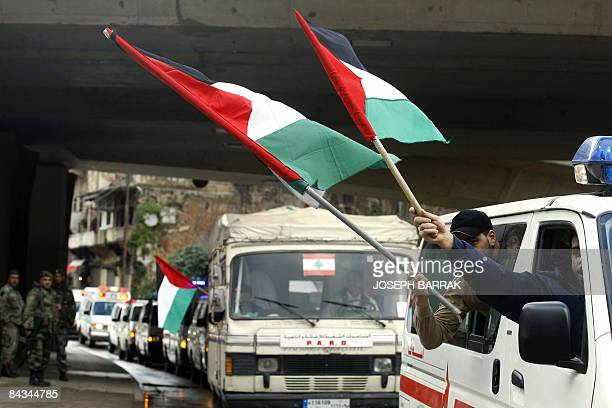 Lebanese soldiers watch a convoy of Palestinian Red Crescent and Islamic leagues a grouping of Islamic associations ambulances as they wave...