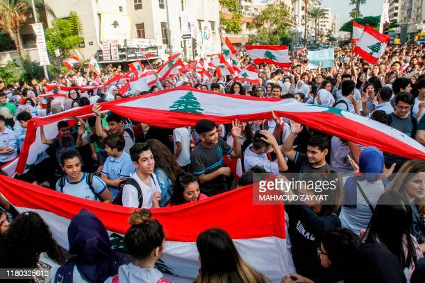 TOPSHOT Lebanese students wave national flags and chant slogans as they gather in an antigovernment demonstration in the southern city of Sidon on...