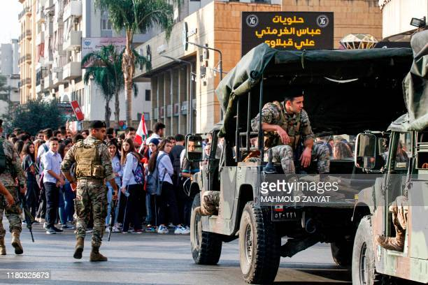 Lebanese students wave national flags and chant slogans as they gather in an antigovernment demonstration before army soldiers in the southern city...