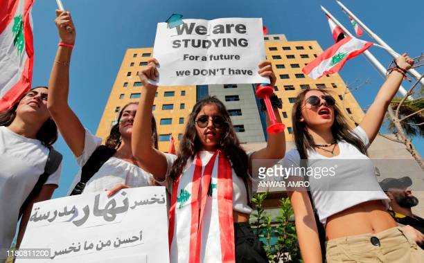Lebanese students wave the national flag and chant slogans as they gather outside the Ministry of Education and Higher Education during ongoing...