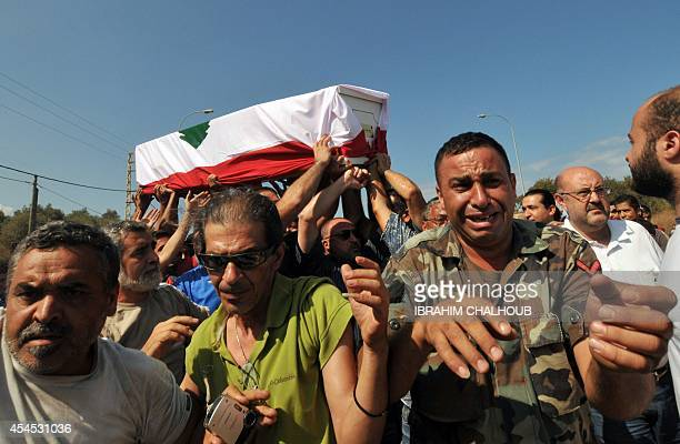 Lebanese Sunni mourners carry the coffin of Lebanese soldier Ali Sayyed draped in his national flag in the village of Qalamun south of the northern...