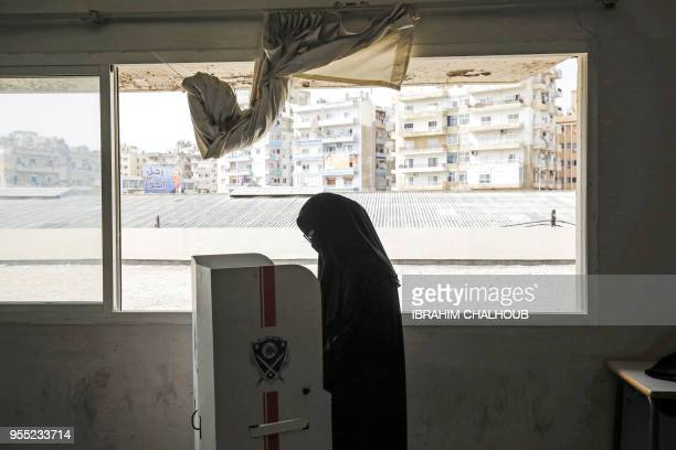 Lebanese Sunni Muslim woman wearing a fullface veil checks her ballot behind a booth as she votes in the first parliamentary election in nine years...