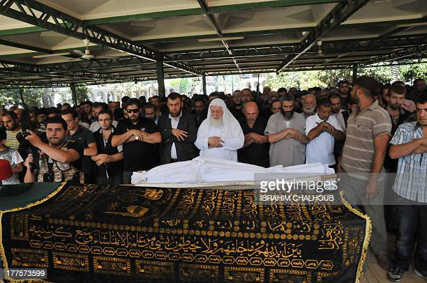 Lebanese Sunni Sheikh Daei alIslam alShahal prays among people during the funeral of a victim of the previous day's bombings in the northern city of...