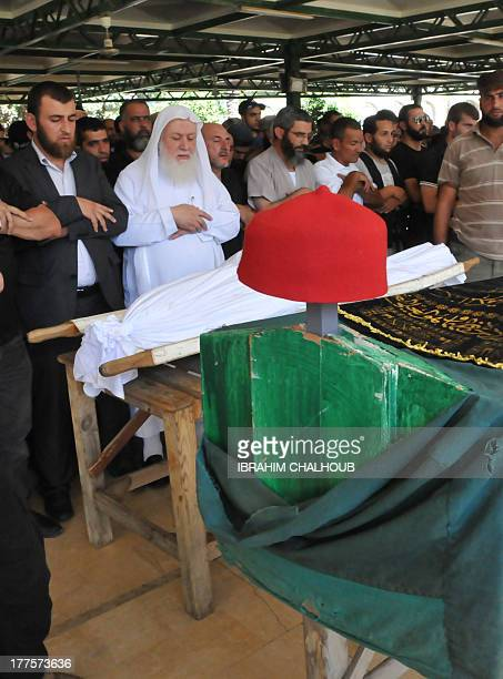 Lebanese Sunni Sheikh Daei alIslam alShahal prays among people in front of the wrapped body of a victim of the previous day's bombings during her...