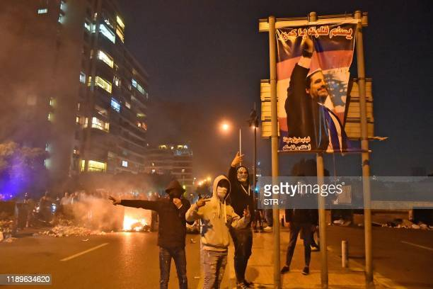 Lebanese supporters of outgoing prime minister Saad Hariri gesture next to a poster bearing his picture as they block a road in the Qasqas...