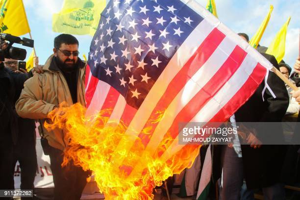 Lebanese supporters of the Shiite Hezbollah movement burn a US flag during a rally against the US president's decision to recognise Jerusalem as the...