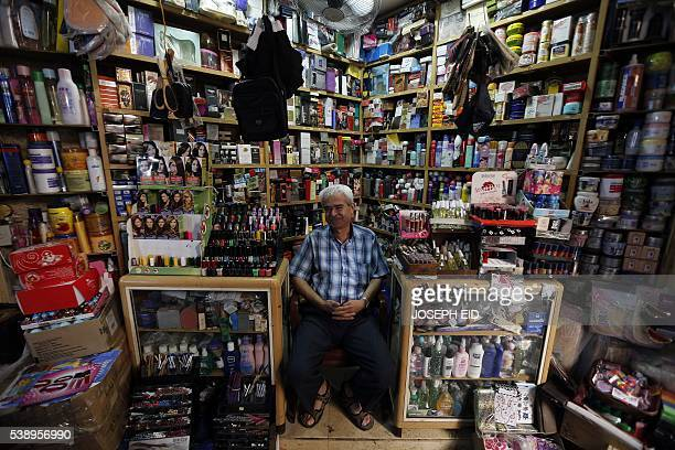 A Lebanese vendor poses in his perfume shop at a market in the old part of the Lebanese southern port city of Sidon south of Beirut on June 9 2016...
