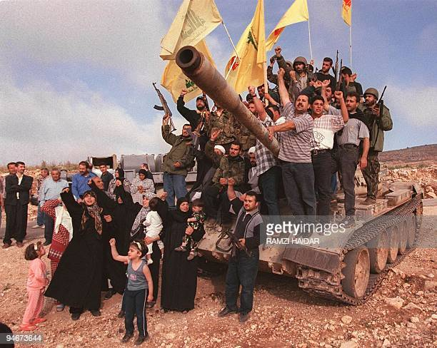Lebanese villagers and Hezbollah fighters pose for a picture on and around a tank abandoned by the Israeliallied South Lebanon Army militia 24 May...