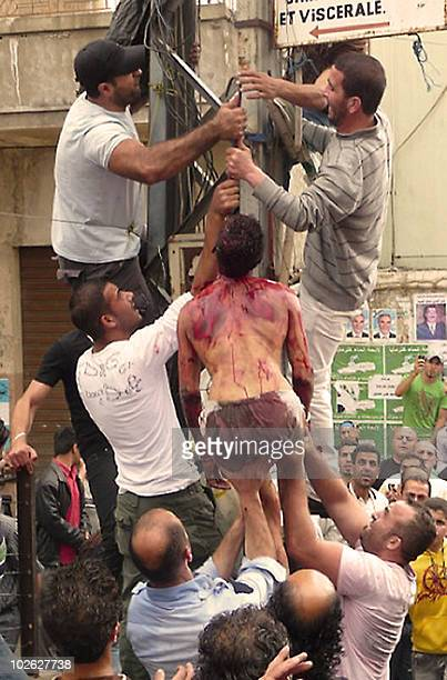 CONTENT Lebanese villagers who lynched an Egyptian murder suspect hang him with a butcher's hook on an electricity pole in the main square of the...