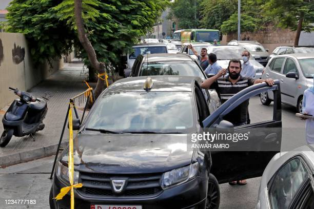 Lebanese wait in a queue outside a closed petrol station in Beirut's Hamra district on August 20, 2021. - Lebanon's energy crisis is dragging people...