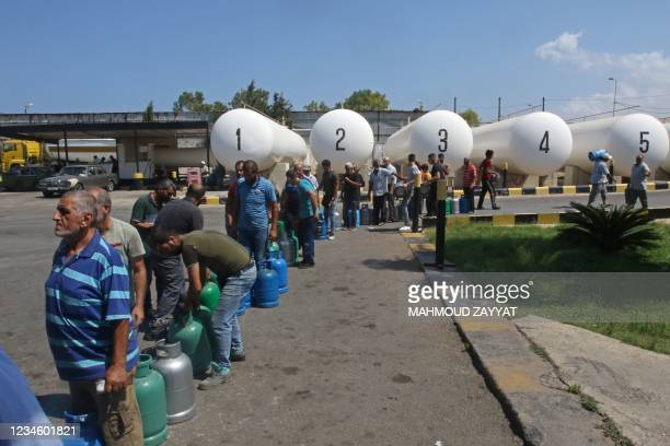 Lebanese wait to fill their gas cylinders in the southern city of Sidon amidst a deepening economic crisis, on August 10, 2021 - Lebanese lined up in...