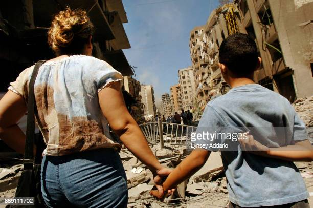 Lebanese walk through the destruction in Beirut's southern suburbs on the first day of the ceasefire between Israel and Lebanon, August 14, 2006....
