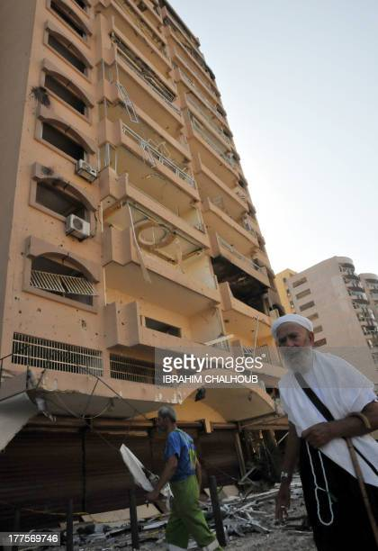 A Lebanese walks past a building that was damaged in a bombing outside AlSalam mosque in the northern city of Tripoli on August 24 2013 Lebanon is to...