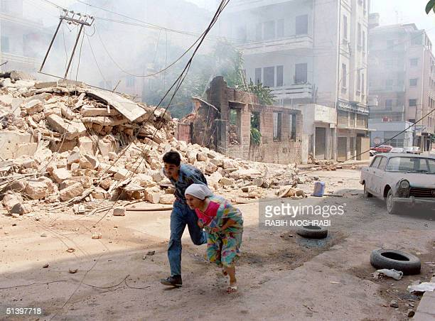 Lebanese woman and son run through west Beirut 13 August 1989 under shellfire as artillery duels continued between Syrian forces Amal Chiite movement...